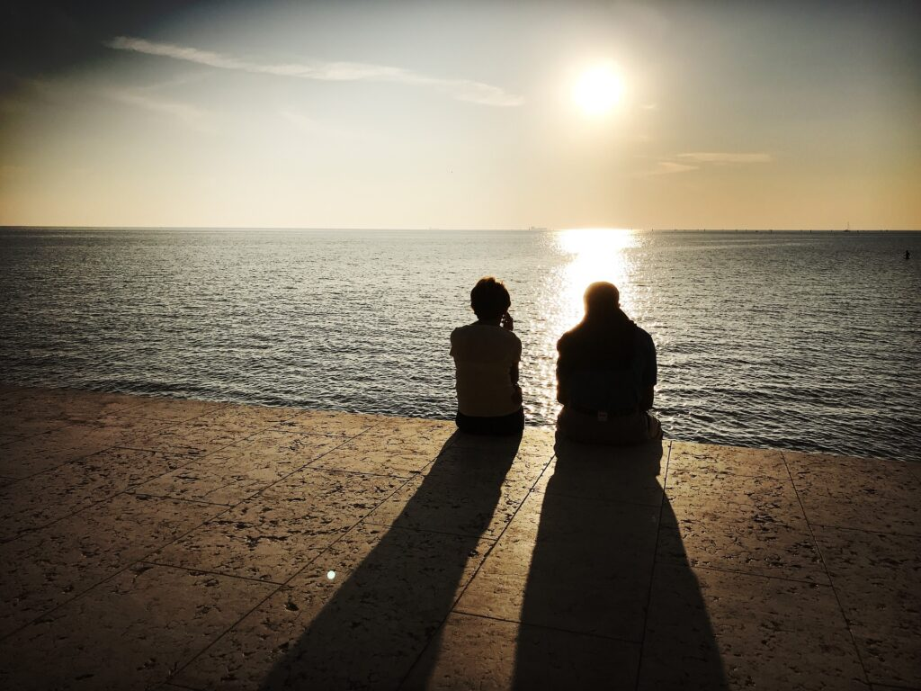 a couple sitting over a water body watching the sunset